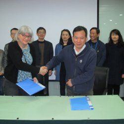 Cathie receiving her contract for the adjunct professorship from Yonghong Hu, with Xiao-Ya Chen (centre) looking on